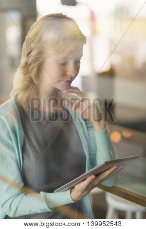 Beautiful woman using digital tablet in café