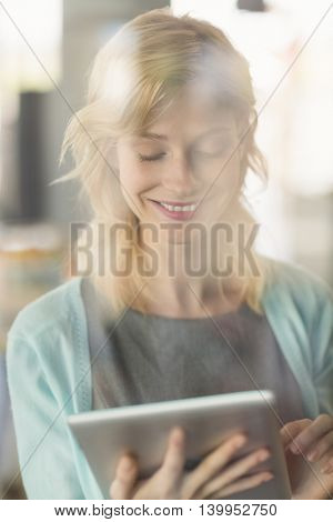 Close-up of beautiful woman using digital tablet in café