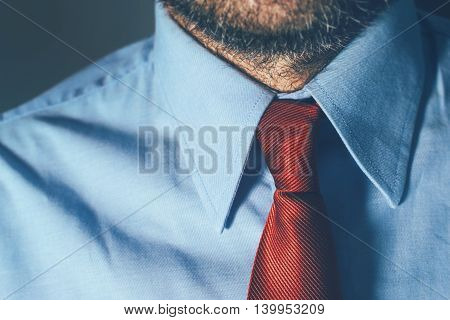 Businessman in blue shirt and red necktie in office with strong shadows suitable for intense business situation such as meeting or contract assignment with uncertain outcome selective focus.
