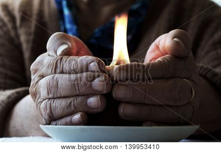 very old senior woman hands wrinkled skin with a candle