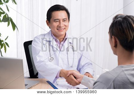 Attractive male doctor shaking a patient's hands in her office