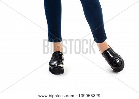 Girl's legs in black shoes. Footwear on thick sole. Glossy leather of high quality. Durable and stylish shoes.