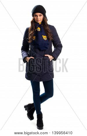 Girl in navy down jacket. Dark pants and ankle boots. Model wears casual winter outfit. High quality waterproof fabric.