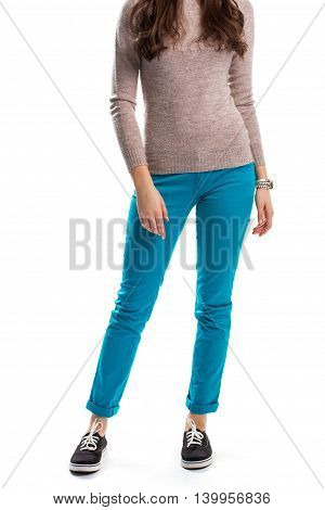 Woman in beige sweatshirt. Slim fit pants and sneakers. Cotton trousers of turquoise color. Simple and comfortable outfit.