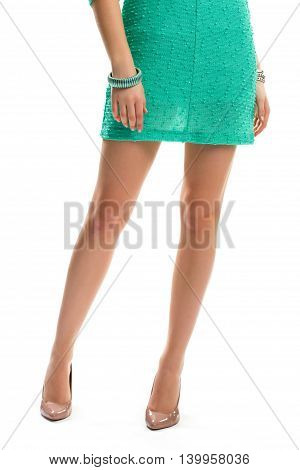 Lady's legs in beige heels. Short dress and bracelet. Evening garment and footwear. Thin summer dress form boutique.