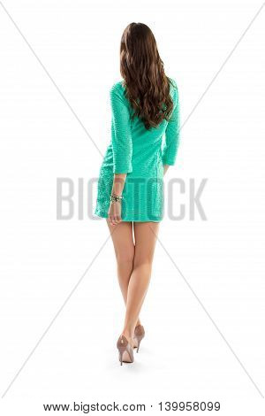 Woman in dress is walking. Short dress with long sleeves. Back view of beautiful model. Night outfit idea.