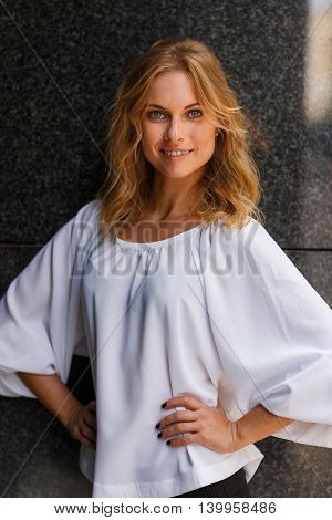 Portrait of smiling cute blond girl in half-growth posing outdoors with hands akimbo