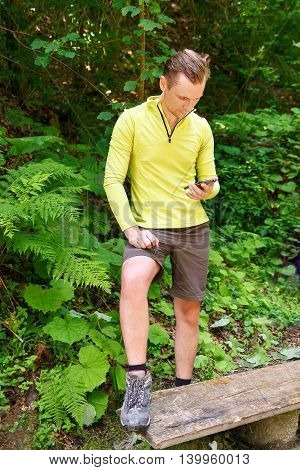 Man hiker determine the location with using smartphone in forest. Lost hiker in forest with mobile satelite navigation device
