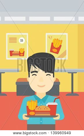 An asian young man holding tray full of junk food on a cafe background. Smiling man in fast food restaurant. Man having lunch in a fast food restaurant. Vector flat design illustration. Vertical