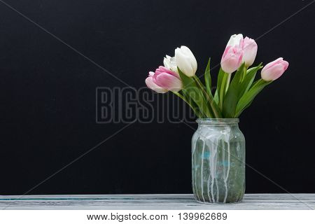 Beautiful pink flowers tulips on wooden table and black board background . Top view with copy space.