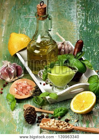 Freshly Made Creamy Pesto Sauce in Glass Gravy Boat with Raw Basil Leafs Ingredients Spices and Olive Oil in White Wooden Tray Arranged on Cracked Wooden background