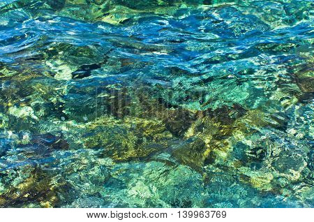Rocky sea floor visible through crystal clear turquoise water of Aegean sea in Greece