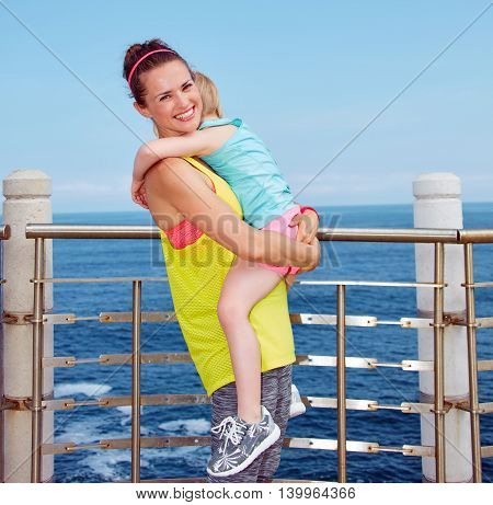Smiling Mother And Child In Fitness Outfit Hugging On Embankment