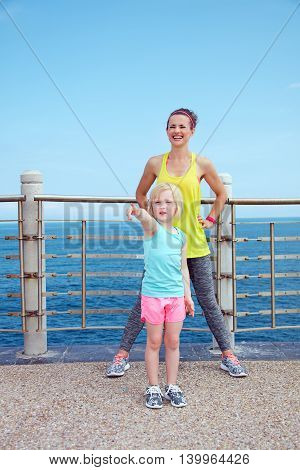 Fitness Mother And Child On Embankment Pointing On Something