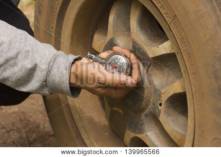 Male using a tire gauge with background rubber suitable for  background safety or background mechanic and check or background man working