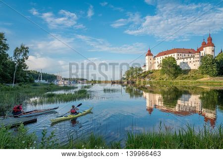 LIDKOPING, SWEDEN - JULY 23, 2016: Tourists kayaking on a summer evening by Lake Vanern and Lacko Castle. Lacko Castle is considered as one of the most beautiful castles in Sweden.