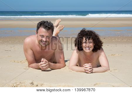 Nude Couple Lying On Warm Sand By A Sea