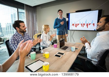 Coworkers applauding a colleague after presentation in the conference room