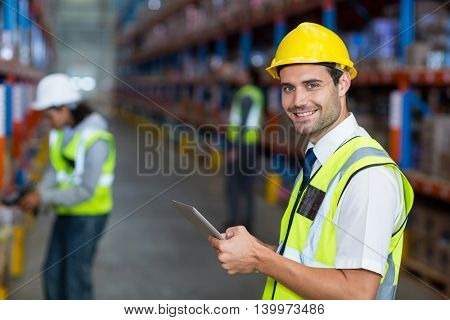 Worker in warehouse looking at camera with yellow safety vest