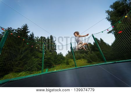Cute boy enjoys jumping and bouncing on trampoline oudoors.