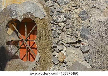 Barred and shuttered window opening in rustic stone wall. Funchal Madeira Portugal