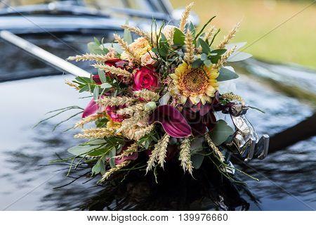Beautiful wedding bouquet on black car hood