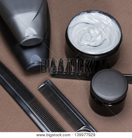 Different hair care and styling products and accessories. Cosmetics and various types of combs on brown textured surface