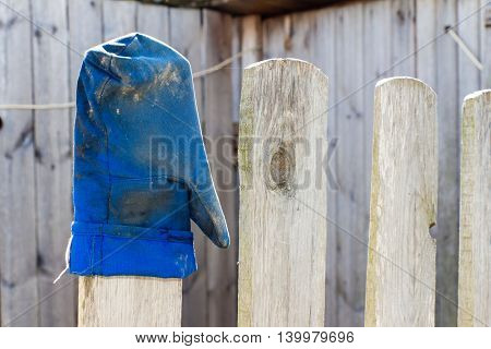 Blue mitten worn on the fence (wood). Gauntlet after work and dirty.
