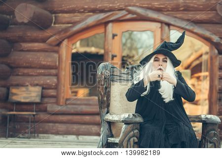 Old man wizard with long grey hair beard in black costume and hat for Halloween gesticulates in wooden chair on log house background