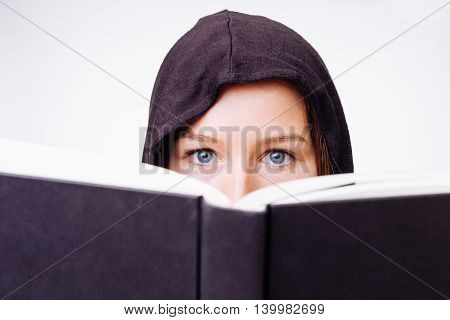 Beautiful young girl peeking over her book