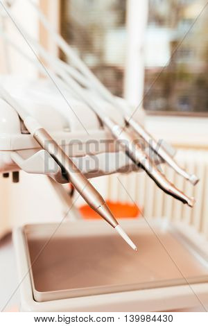 Dentist's handpieces placed on dentist tool rack with focus on air water spray.