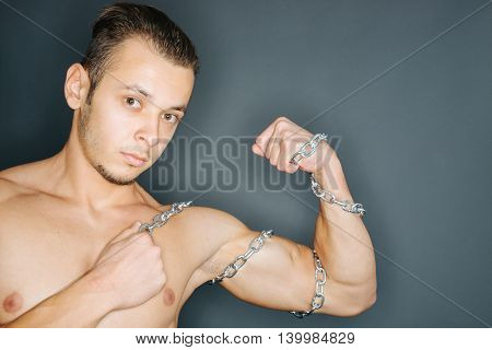 Closeup of a young man with chains around tense biceps