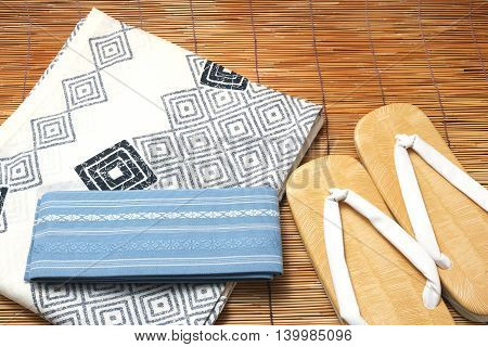 Japanese yukata and a band for men on bamboo blinds. Concept of Japanese summer.