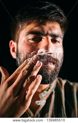 Drug addicted man having cocaine on his face. Chiaroscuro photography