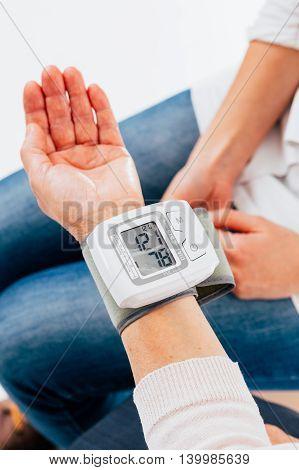 Digital tensiometer on female hand measuring blood pressure