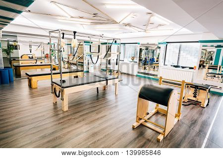 Room full of pilates equipment: exochairs ladder barrel reformer cadillac and trapeze table