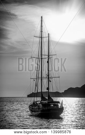 Old ship sailing to the sunset. Dramatic dark evening sea view. Black and white
