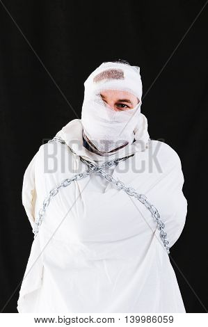 Mentally insane patient in chains and straitjacket