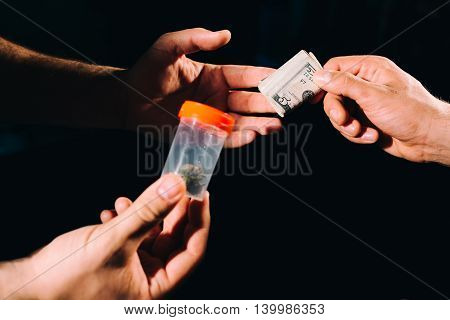Hands of a person addicted to drugs buying marijuana