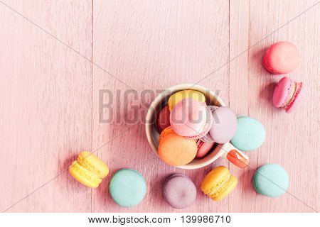 Vintage colorful macaroons on pink wooden background.