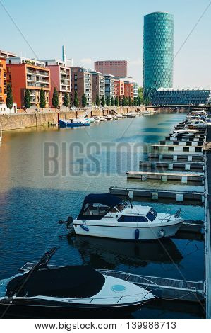 View of the boats anchored on Main's shore residential buildings and Westhafen tower in Frankfurt Germany