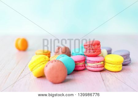 colorful macarons on a pink wooden table