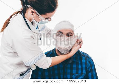 Young nurse applying a bandage to a man who had a head trauma - isolated on white.