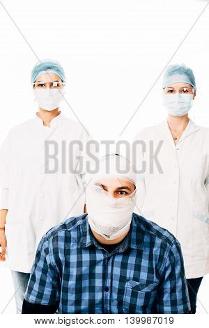 Man in bandage and nurses against him - isolated on white.