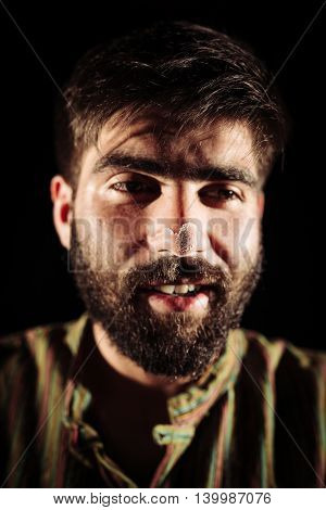 Closeup of a bearded junkie with cocaine powder on his nose