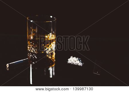 Cocaine alcohol and five dollars on glassy black background.