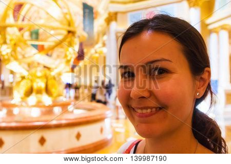 LAS VEGAS NV USA - JULY 13 2013: Happy female tourist in The Venetian Hotel near the entrance golden statue.