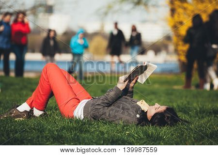 Lying woman reading a book and relaxing in the park.