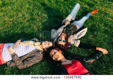 Careless happy three woman lying on the green lawn