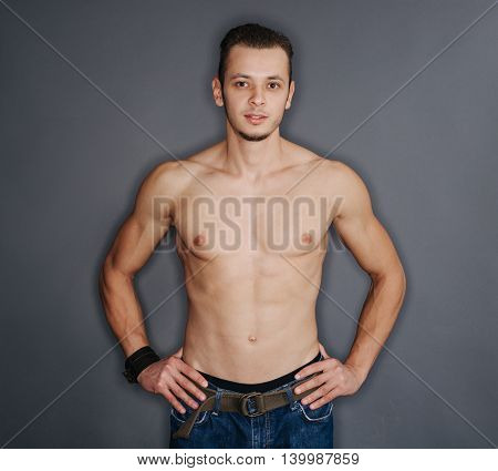Young body art athlete with well trained pecs and abs and blue jeans.